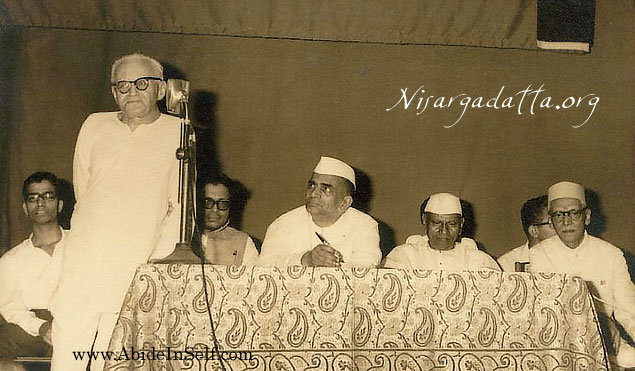 Frydman speaking at a function in Bombay. Nisdargadatta Maharaj is sitting second from the right.