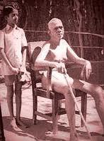 V. Ganesan standing behind Ramana Maharshi in the 1940s.