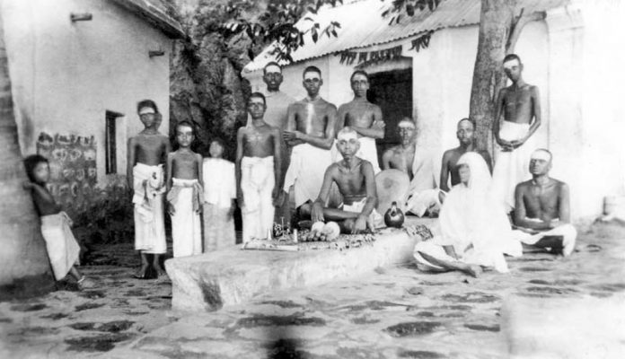 Bhagavan and his mother sitting in courtyard of Skandashram. Kunju Swami is sitting on the right